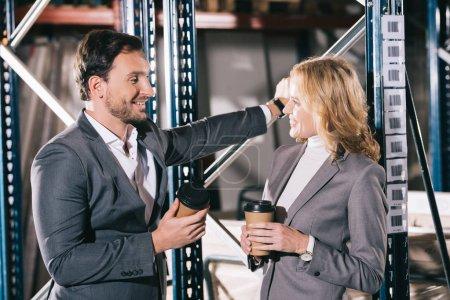 Photo pour Deux hommes d'affaires souriants parlant dans un entrepôt tout en tenant des tasses jetables - image libre de droit