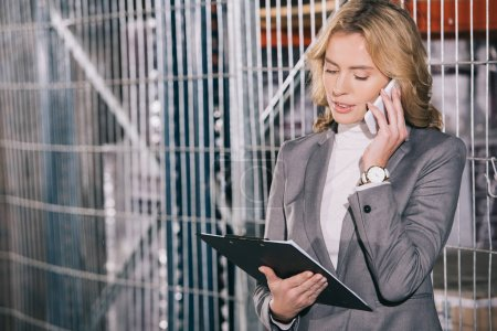Photo pour Attractive business woman talking on smartphone and holding clipboard in warehouse - image libre de droit