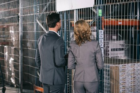 Photo for Back view of businessman and businesswoman looking at racks in warehouse - Royalty Free Image