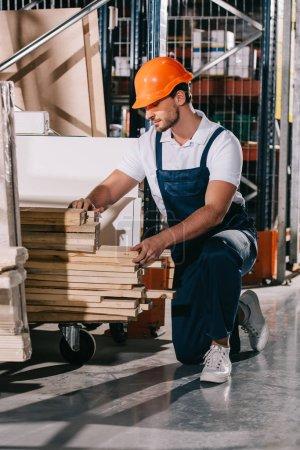 Foto de Trabajadores de almacén de rodillas cerca de rack con tableros de madera. - Imagen libre de derechos