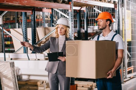 businesswoman in helmet pointing with hand while standing near loader holding cardboard box