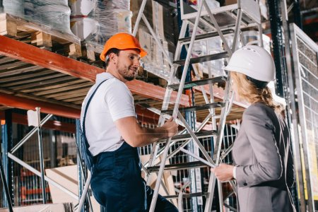 smiling warehouse worker standing on ladder and looking at businesswoman in helmet