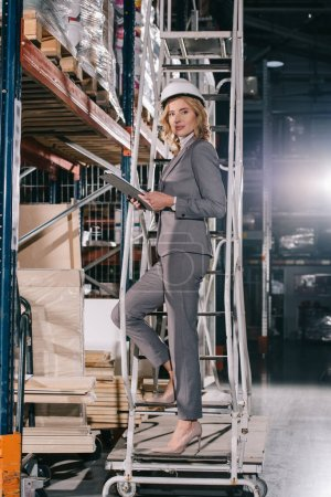 Photo for Businesswoman in formal wear and helmet standing on stepladder with clipboard and looking at camera - Royalty Free Image