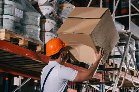 Photo for Warehouse worker holding cardboard box while standing on stepladder - Royalty Free Image