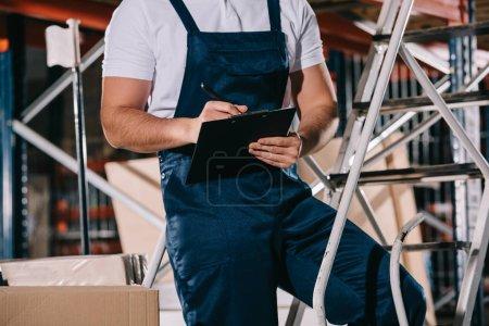 Photo pour Vue en coupe de l'ouvrier de l'entrepôt en salopette écriture sur le presse-papiers de l'entrepôt - image libre de droit