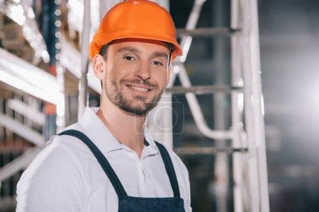 handsome warehouse worker in helmet smiling at camera