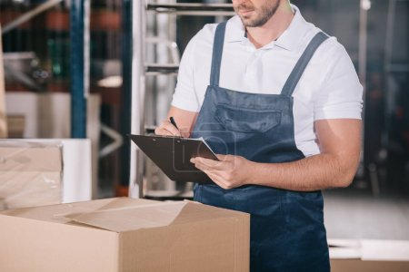 Photo pour Cropped view of warehouse worker writing on clipboard while standing near cardboard box - image libre de droit