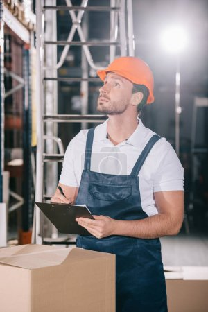 Photo for Concentrated warehouse worker looking away while writing on clipboard - Royalty Free Image
