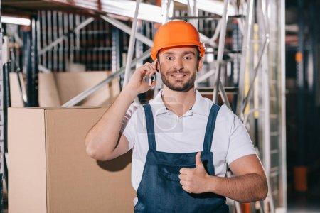 Photo pour Travailleur souriant entrepôt parlant sur smartphone, regardant la caméra et montrant pouce vers le haut - image libre de droit