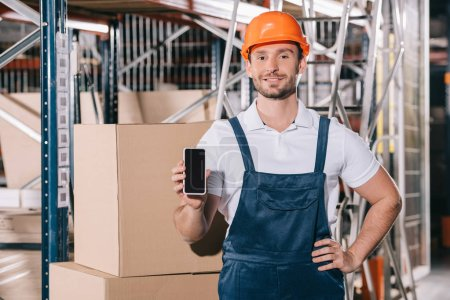 smiling loader standing with hand on hip and showing smartphone with blank screen