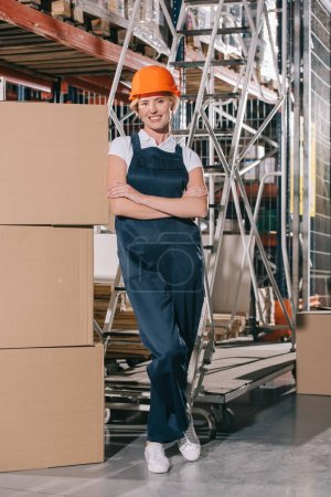 Photo pour Smiling workwoman looking at camera while standing near cardboard boxes with crossed arms - image libre de droit