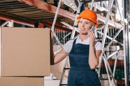 Photo for Smiling workwoman talking on smartphone while standing near cardboard boxes - Royalty Free Image