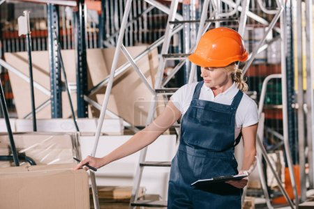 Photo for Workwoman in overalls and helmet holding clipboard while checking cardboard box - Royalty Free Image