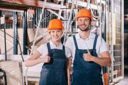Photo pour Des employés d'entrepôt joyeux montrant leurs pouces levés et souriant à la caméra - image libre de droit