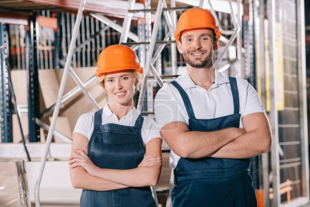 Photo pour Travailleurs d'entrepôt joyeux debout, les bras croisés et souriant devant la caméra - image libre de droit