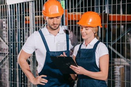 Photo pour Souriant femme de travail tenant presse-papiers tout en se tenant près de l'ouvrier concentré - image libre de droit