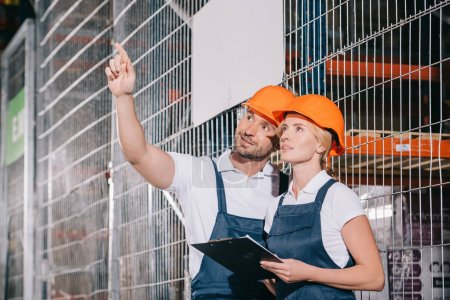 Photo for Workwoman holding clipboard while standing near workman looking away and pointing with finger - Royalty Free Image