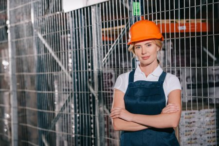 Photo for Attractive workwoman in overalls and helmet standing with crossed arms and looking at camera - Royalty Free Image
