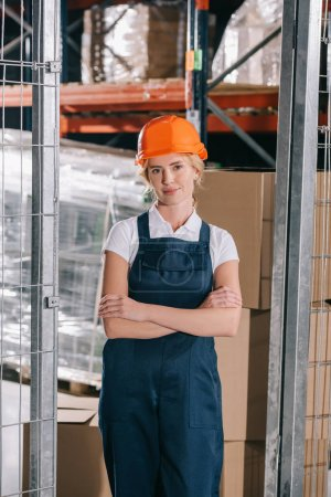 attractive workwoman in overalls and helmet standing with crossed arms and looking at camera