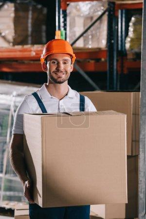 Photo pour Chargeur joyeux souriant à la caméra tout en tenant boîte en carton - image libre de droit