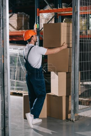 Photo pour Warehouse worker in overalls and helmet taking cardboard box from stack - image libre de droit