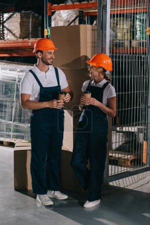 Photo for Smiling warehouse workers looking at each other while holding coffee to go - Royalty Free Image