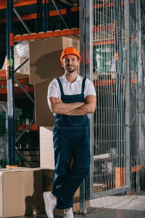 Photo pour Handsome warehouse worker smiling at camera while standing near cardboard boxes with crossed arms - image libre de droit
