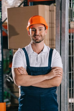 Photo for Handsome warehouse worker smiling at camera while standing with crossed arms - Royalty Free Image