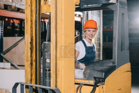 Photo for Attractive workwoman sitting in forklift loader and smiling at camera - Royalty Free Image