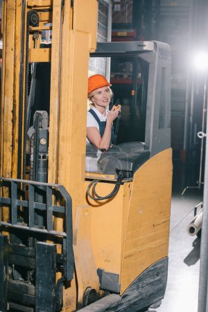 Photo for Smiling workwoman sitting in forklift loader, talking on walkie talkie and looking away - Royalty Free Image