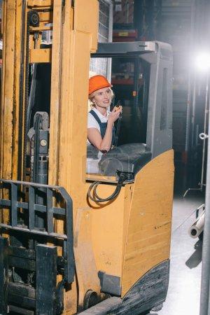 smiling workwoman sitting in forklift loader, talking on walkie talkie and looking away