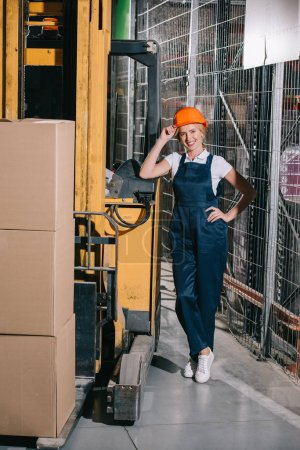 Foto de Trabajadora alegre de pie cerca del cargador de carretillas elevadoras con la mano en la cadera, tocando casco y mirando la cámara. - Imagen libre de derechos
