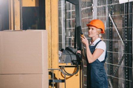 Photo pour Une travailleuse souriante qui parle sur un talkie pendant qu'elle se tient debout près d'une chargeuse à fourche - image libre de droit