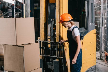Photo for Workwoman in overalls and helmet standing near foklift loader in warehouse - Royalty Free Image