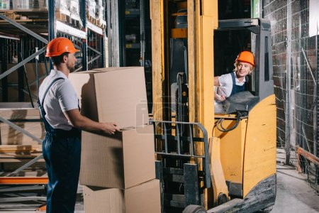 smiling workwoman sitting in forklift loader and looking at worker holding cardboard box