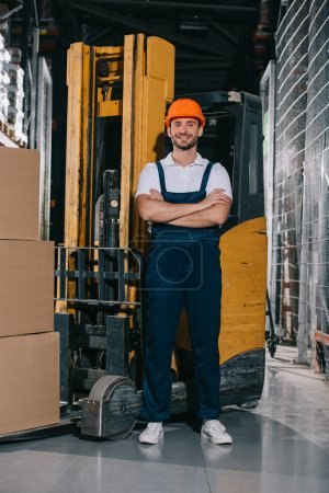 Photo for Handsome warehouse worker smiling at camera while standing near forklift loader with crossed arms - Royalty Free Image