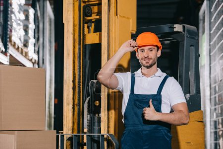 Photo for Smiling warehouse worker touching helmet and showing thumb up while standing near forklift loader - Royalty Free Image