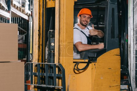 Photo for Smiling warehouse worker showing thumb up and looking at camera while operating forklift loader - Royalty Free Image