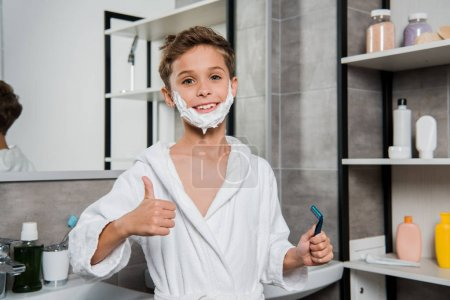Photo for Happy boy with shaving foam on face holding razor and showing thumb up - Royalty Free Image