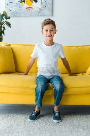Photo for Happy boy in white t-shirt sitting on yellow sofa - Royalty Free Image