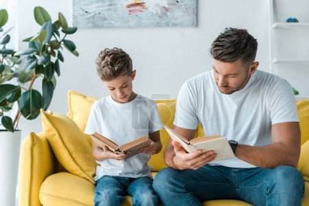 Photo pour Beau père et fils lisant des livres à la maison - image libre de droit