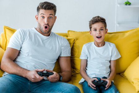 KYIV, UKRAINE - OCTOBER 2, 2019: surprised father and son playing video game at home