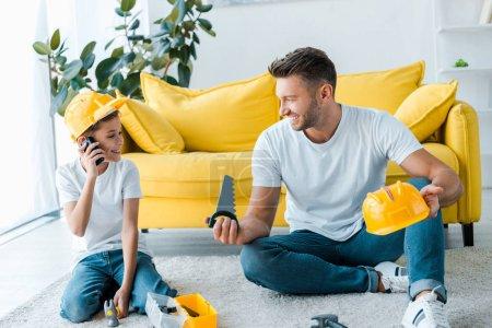 Photo pour Joyeux père regardant son fils jouer avec le talkie walkie - image libre de droit