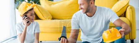 Photo pour Photo panoramique d'un père heureux regardant son fils jouer avec un talkie walkie - image libre de droit