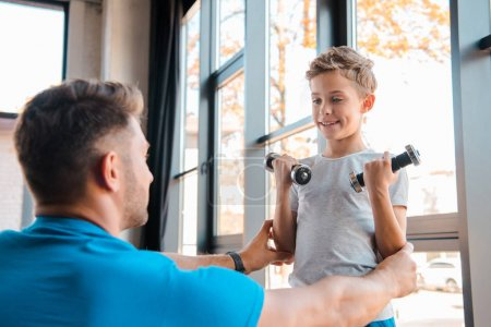 Photo for Selective focus of happy father touching cute son weightlifting dumbbells - Royalty Free Image