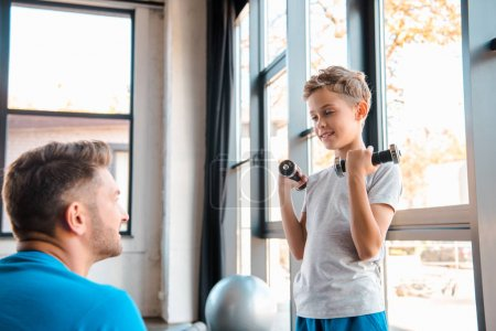 Photo for Selective focus of happy father looking at son weightlifting dumbbells - Royalty Free Image