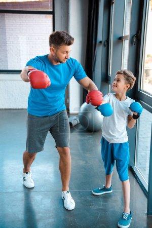 Photo pour Un père regarde un mignon fils en gants de boxe pendant qu'il fait de l'exercice au gymnase - image libre de droit