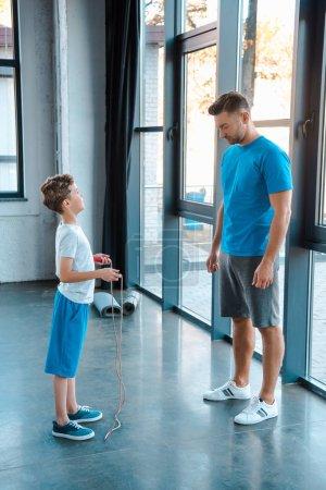 Photo pour Beau père se tenant près d'un enfant avec une corde à sauter au gymnase - image libre de droit