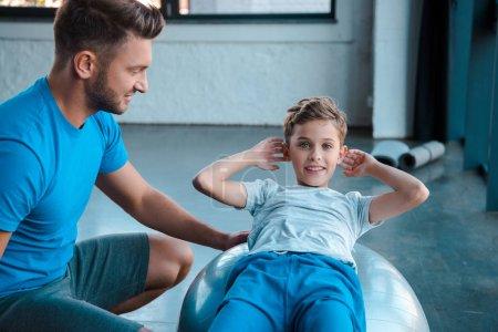 Photo pour Joyeux père près enfant heureux travaillant sur le ballon de fitness - image libre de droit