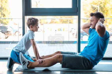 Photo pour Vue latérale d'un fils mignon regardant un père en train de faire de l'exercice - image libre de droit